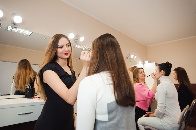 Make-up artiest doet professionele make-up van jonge vrouw.