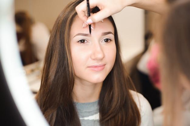 Make-up artiest doet professionele make-up van jonge vrouw.