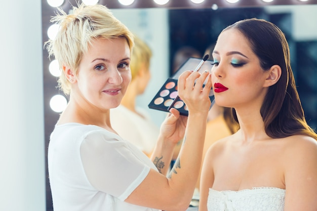 Make-up artiest doet professionele make-up van jonge vrouw