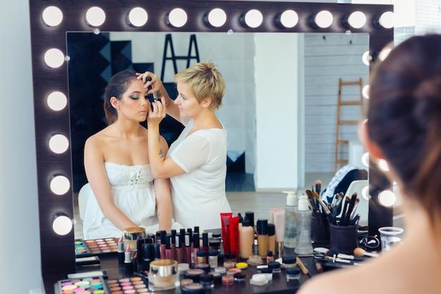 Make-up artiest doet professionele make-up van jonge vrouw