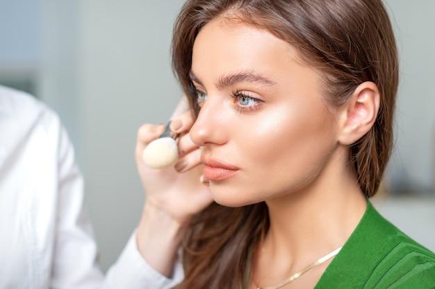 Make-up artiest droge cosmetische tonale stichting toe te passen op het gezicht van de jonge vrouw met behulp van penseel in de schoonheidssalon