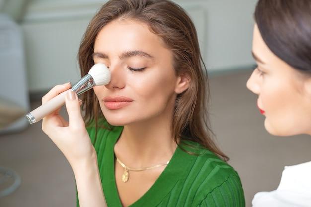 Make-up artiest droge cosmetische tonale stichting toe te passen op neus van jonge blanke vrouw met behulp van penseel in de schoonheidssalon
