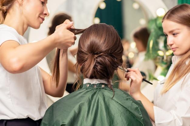 Make-up artiest en kapper bereiden jonge vrouw in een schoonheidssalon voor