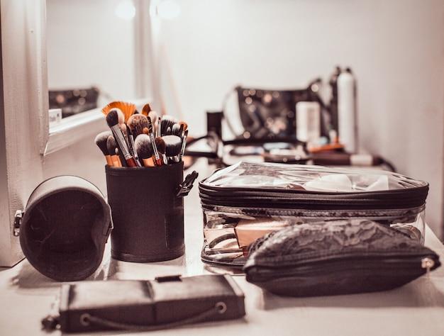 Make-up artiest gereedschap-make-up penselen en cosmetische producten op de tafel met een spiegel.