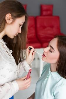 Make-up artiest glans toe te passen op de lippen van de vrouw