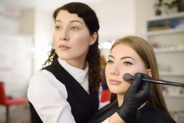 Make-up artiest het aanbrengen van de toon van de stichting met behulp van speciale borstel op gezicht jonge mooie model.