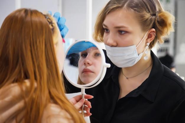 Make-up artiest maakt wenkbrauwcorrectie schattige mooie jonge vrouw in de schoonheidssalon. klantenservice in interieur salon