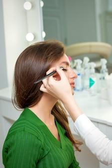 Make-up artiest past oogschaduw poeder toe op de ogen van jonge blanke vrouw met penseel in de schoonheidssalon