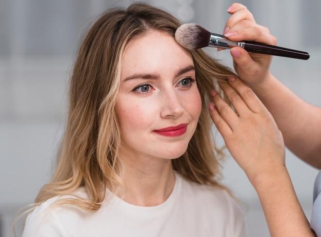 Make-up artiest poederende voorhoofd van de vrouw