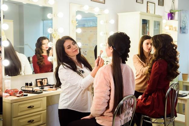 Make-up artiest professioneel doen maakt omhoog van jonge vrouw. school van visagisten