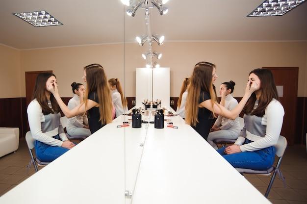 Make-up artiest professioneel doen maakt omhoog van jonge vrouw.