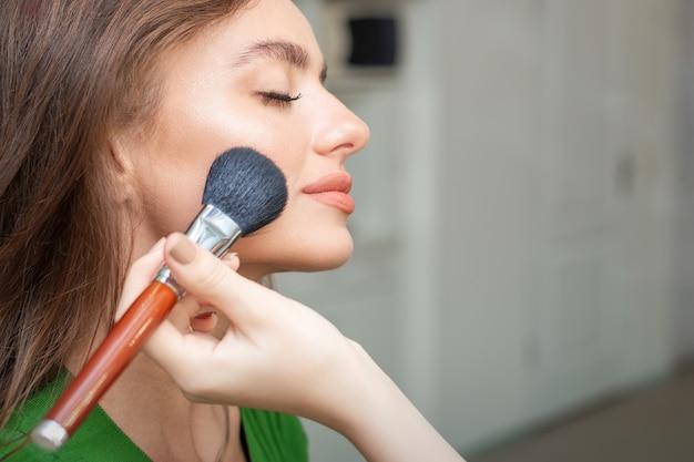 Make-up artiest professionele make-up van tonale stichting toe te passen op het gezicht van mooie jonge blanke vrouw in make-up kamer. basis voor make-up.