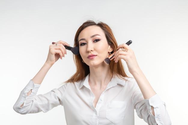 Make-up artiest, schoonheid en cosmetica concept - koreaanse vrouwelijke visagist met make-up kwasten op witte achtergrond