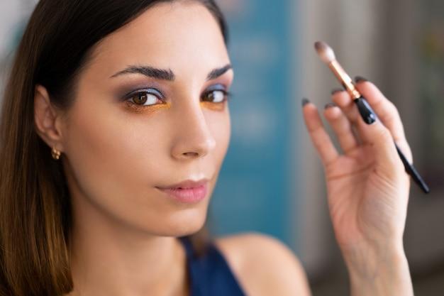 Make-up artiest toepassing van heldere oogschaduw basiskleur op model van het oog