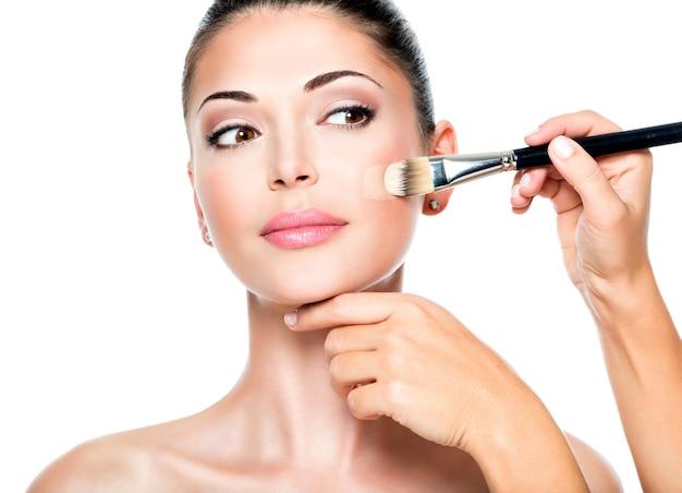Make-up artiest vloeibare tonale foundation toe te passen op het gezicht van de vrouw
