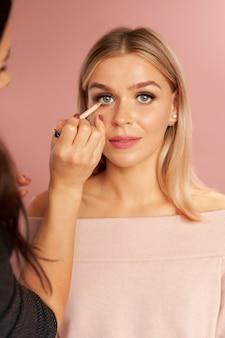 Make-up artist paste eyelinerpotlood toe op een jonge blonde vrouw