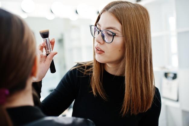 Make-up artist werk in haar schoonheidssalon studio salon. vrouw toepassing door professionele make-up meester.