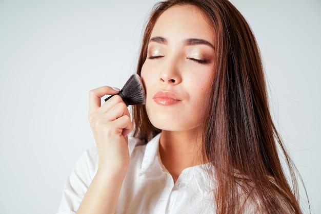 Make-up borstel kabuki ter beschikking van lachende aziatische jonge vrouw met donkere lange haren op wit