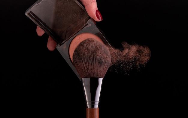 Make-up borstel spuiten poeder op zwarte achtergrond