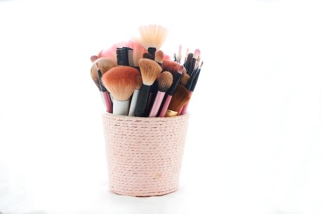 Make-up borstels in een pot op wit wordt geïsoleerd