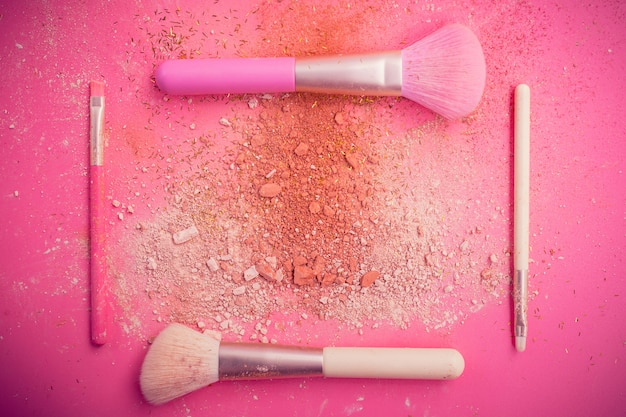 Make-up borstels met poeder op roze achtergrond