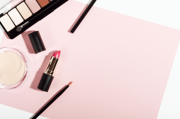 Make-up cosmetica bovenaanzicht op roze trendy achtergrond.