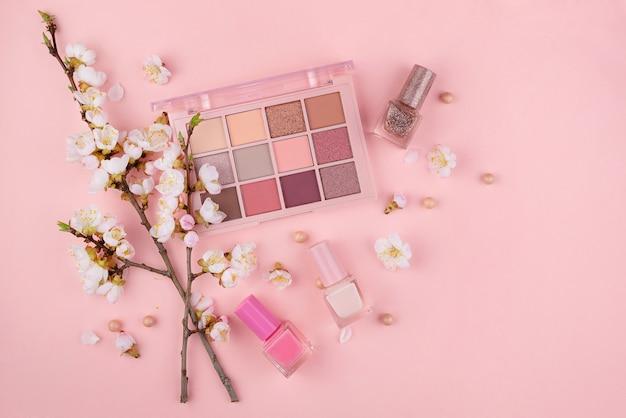 Make-up cosmetica en kersenbloesem op een roze muur. close-up met ruimte voor tekst.