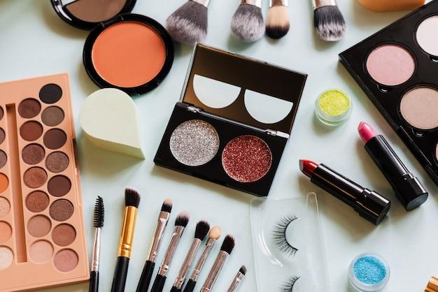 Make-up en borstels bovenaanzicht op witte tafel. vrouwen op de werkvloer
