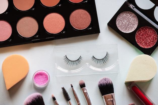 Make-up en borstels bovenaanzicht op witte tafel.