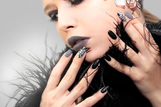 Make-up en manicure met strass steentjes en decoratie op het gezicht van het meisje.