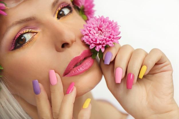 Make-up en manicure op lange nagels van een vrouw met asters.