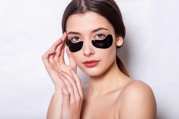 Make-up en zwarte hydrogel ooglapjes gezichtshuid. onder de ooghuid zwarte vlek. close-up van mooie jonge vrouw gezicht met hydraterende collageen masker pad op gezonde frisse gezichtshuid witte achtergrond