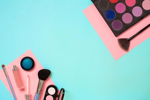 Make-up essentials set professionele make-up kwasten crèmes en schaduwen in potten op blauwe achtergrond