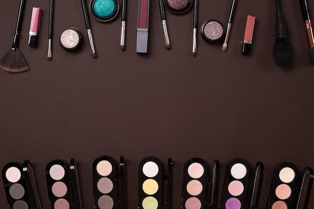 Make-up essentials set professionele make-up kwasten crèmes en schaduwen in potten op donkere achtergrond