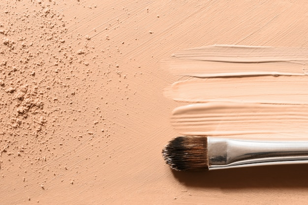Make-up foundation, beige concealer vlekken, gezichtspoeder en cosmetische make-up kwast