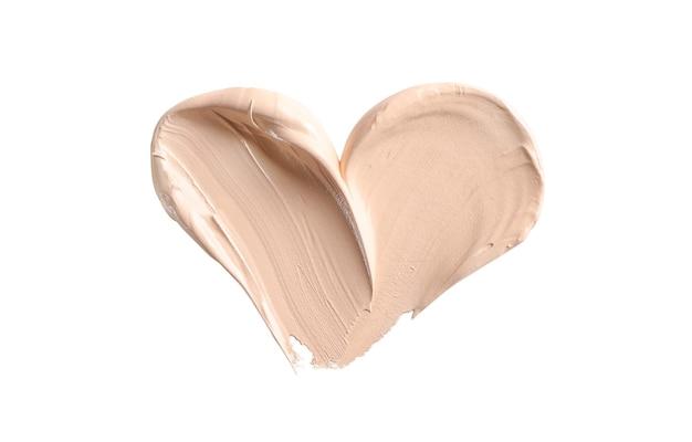 Make-up foundation, cosmetische crème uitstrijkje in vorm van hart geïsoleerd op wit