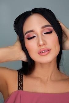 Make-up in roze tinten op een vrouw met lang zwart haar op een witte muur. concept van cosmetica of oogschaduw, foto's voor diploma's voor make-upartiesten.