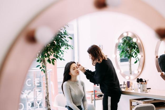 Make-up kunstenaar behandelt het gezicht van de vrouw met oogschaduwen