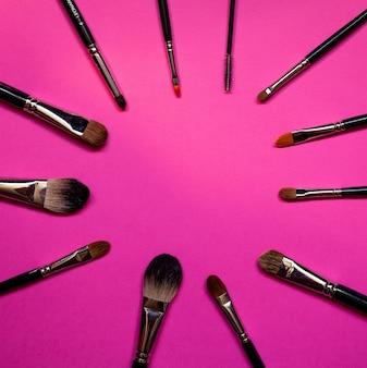 Make-up kwast liggen op een roze achtergrond.