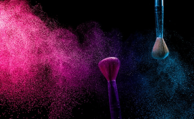 Make-up kwast met blauw en roze poeder.