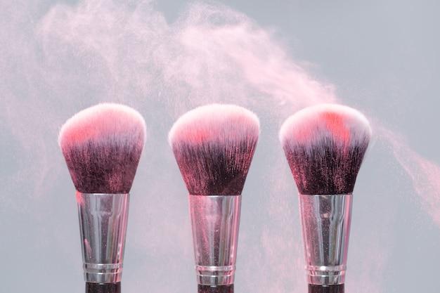 Make-up kwast met roze poeder spatten explosie op grijs