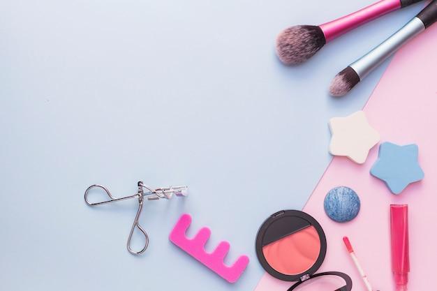 Make-up kwast; ster spons; roze blusher; wimperkruller en lippenstift op dubbele achtergrond