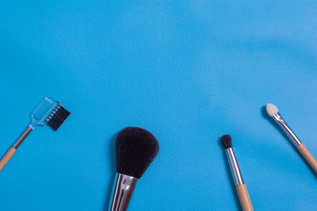 Make-up kwasten, alledaagse make-up tools. cosmetische essentials op blauwe achtergrond, close-up.