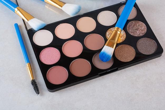 Make-up kwasten met foundation op grijs.