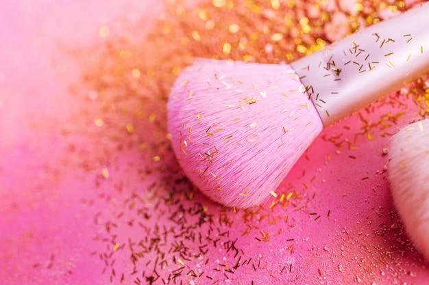 Make-up kwasten met poeder op roze oppervlak