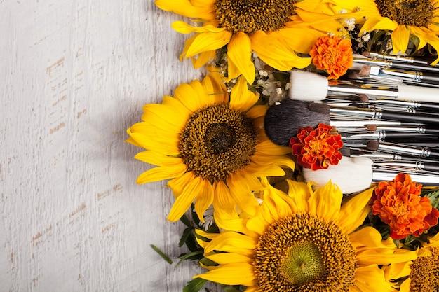 Make-up kwasten naast prachtige wilde bloemen op houten achtergrond