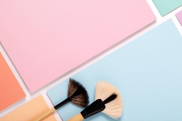 Make-up kwasten op pastel gekleurd papier, bovenaanzicht