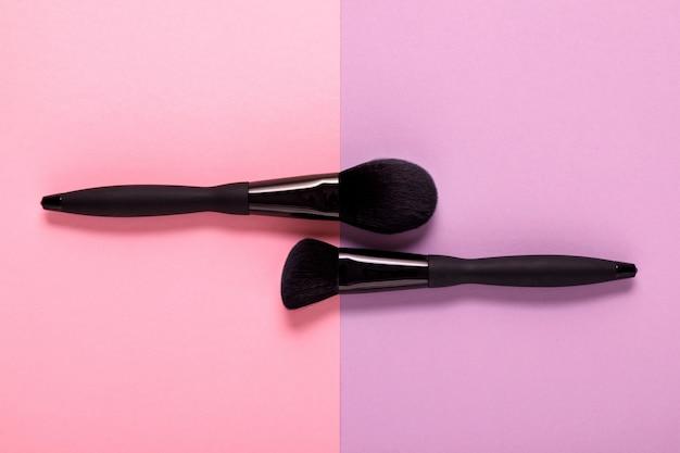 Make-up kwasten op pastel papier roze, bovenaanzicht