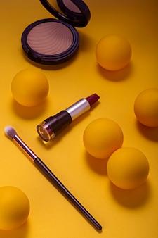Make-up lippenstift en cosmetica op geel oppervlak van bovenaf gezien.