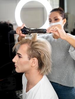 Make-up man met behulp van stijltang op zijn haar